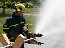 Ein Helfer quetscht eine Wasserleitung mit einem hydraulischen Rettungsspreizer ab.