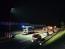 Nächtliche Unfallstelle auf einer Autobahn. Im Vordergrund ein Lichtmasthänger und der Mehrzwecklastwagen der Fachgruppe Beleuchtung, im Hintergrund Fahrzeuge der Polizei, Autbahnmeisterei und verschiedener Bergungsunternehmen sowie ein verunfalltes Mot