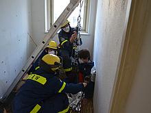 Ein Verletztendarsteller wird von drei Helfern mittels Flaschenzug durch einen Deckendurchbruch gerettet.
